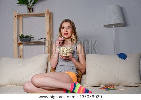 Pretty girl is watching tv with interest and amazement. She is sitting on sofa and eating popcorn