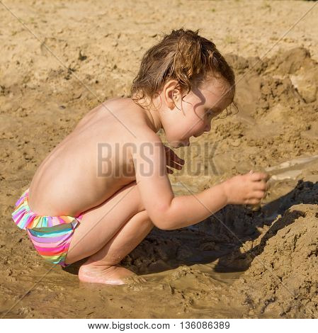 Baby playing in sand on the river beach