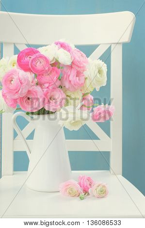 Pink and white ranunculus flowers in vase on chair, retro toned