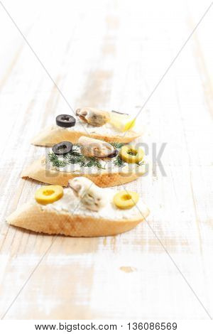 Tasty various italian sandwiches with seafood against rustic wooden background. Crostini with cheese mussels and sliced olives close up with selective focus