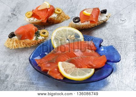 Tasty various italian sandwiches with seafood against rustic wooden background. Crostini with cheese red fish lemon and sliced olives close up with selective focus