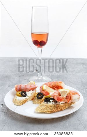 Tasty various italian sandwiches with seafood against rustic wooden background. Crostini with cheese shrimps and olives on white plate glass of wine close up with selective focus