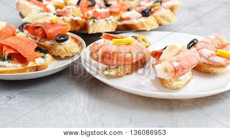 Tasty various sandwiches with seafood against rustic wooden background. Crostini with cheese shrimps mussels red fish crab sticks lemon olives on plates close up with selective focus
