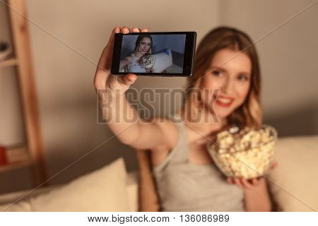 Happy young girl is making selfie at home. She is sitting on sofa and holding a bowl of popcorn. Lady is smiling. Focus on mobile phone in her hand