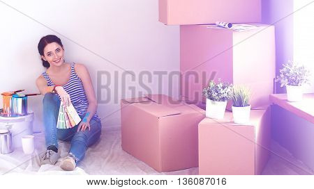 Woman choosing paint colour from swatch for new home sitting on wooden floor.