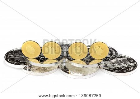 Four gold coins standing on silver coins isolated on white background
