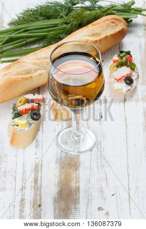 Tasty various italian sandwiches with seafood against rustic wooden background. Crostini with cheese crab sticks and olives bread herbs and wine close up with selective focus