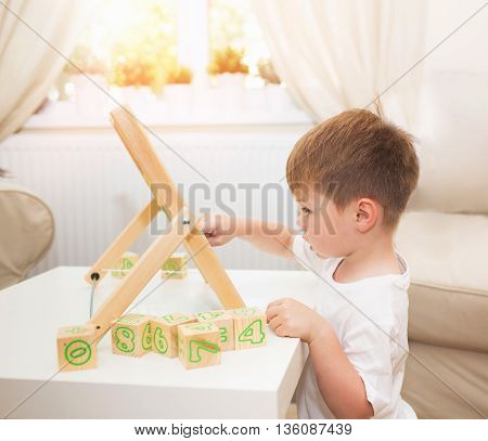Little boy playing with abacus toy at home