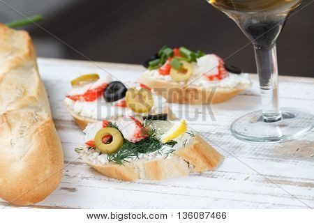 Tasty various italian sandwiches with seafood against rustic wooden background. Crostini with cheese crab sticks and olives bread and wine close up horizontal view with selective focus