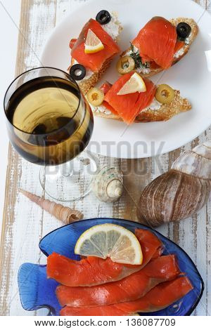 Tasty various italian sandwiches with seafood against rustic wooden background. Crostini with cheese red fish and olives on white plate and wine top view