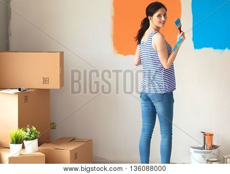 Happy smiling woman painting interior wall of new house.