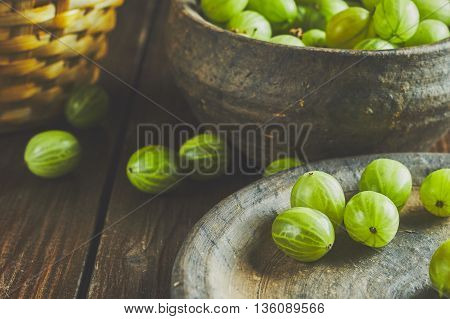 Gooseberries on dark background in clay bowl and plate