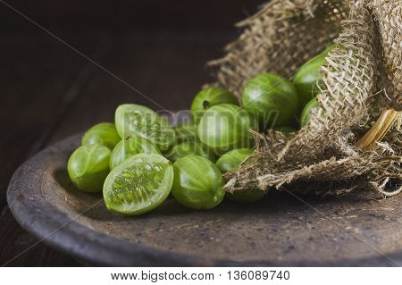 Gooseberries on dark wooden background coming out of burlap bag. Copy space