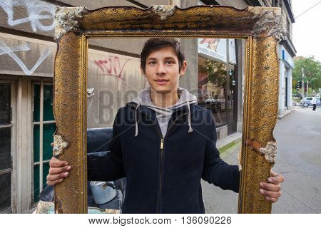 ZAGREB, CROATIA - OCTOBER 14, 2013: Roma boy holding picture frame at garbage dump.