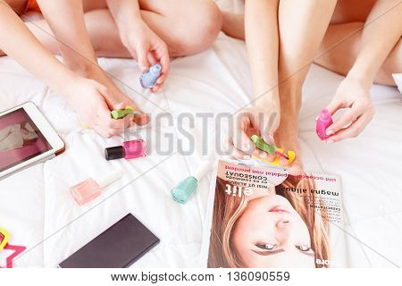 Young girls making pedicure at home together. They are sitting on bed near fashionable magazine, mobile phone and tablet
