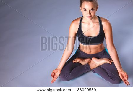 Young woman sitting on the floor in lotus position .