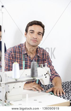 Confident Tailor Sitting At Workbench In Factory