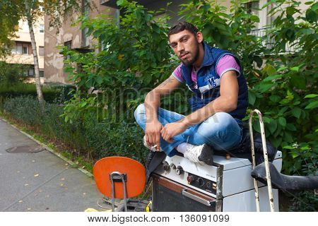 ZAGREB, CROATIA - OCTOBER 15, 2013: Young Roma man posing for camera at garbage dump.
