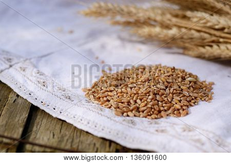 Grains of wheat on vintage linen tablecloths. Selective focus macro shot. Ingredients for bread on an old wooden table. Rustic Still Life