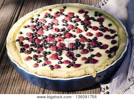 Sunny Photo with a morning breakfast in a rustic style. Cheesecake with raspberries and blueberries on wooden table. Selective focus picture