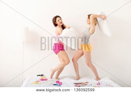 Carefree young women fighting with pillows at pajama party. They are standing on bed and smiling