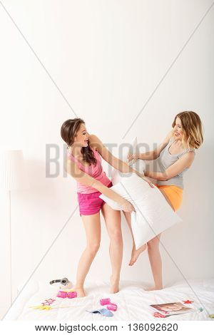 Attractive two girls having pillow fight. They are standing in pajamas on bed at home. Friends are looking at each other and laughing