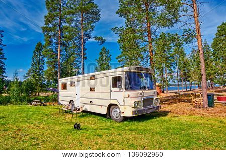 HUDIKSVALL, SWEDEN - CIRCA AUGUST 2015: Big Old American RV / Camping Car in Pine Forest Setting