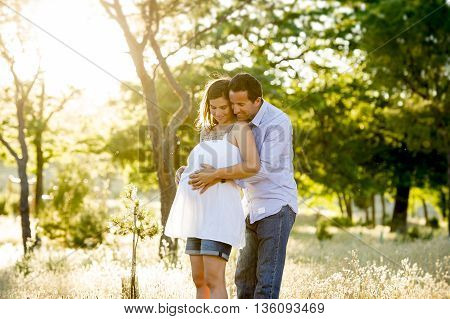 young happy beautiful couple in love walking together on grass and trees park landscape on sunset in summer with man touching pregnant belly of his woman in family concept