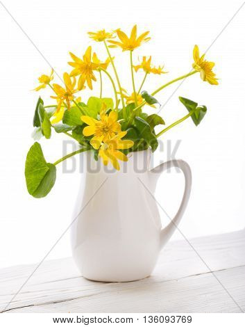 Yellow flowers in a white vase on a white background. The vase (jug) costs on white boards. Close up small depth of sharpness