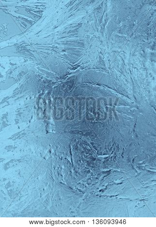 Small frosty patterns on glass in light blue tones. Vertical orientation of a shot