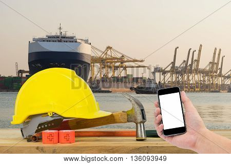 Hand holding the black smartphone with Yellow Safety Helmet on foreground of huge container cargo ship at harbor