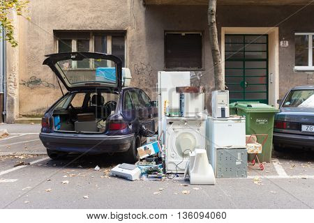 ZAGREB, CROATIA - OCTOBER 15, 2013: Parked car with opened trunk next to garbage dump.