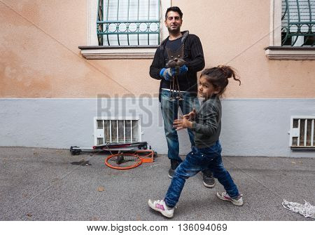 ZAGREB, CROATIA - OCTOBER 14, 2013: Roma father and daughter collecting waste at street garbage dump.