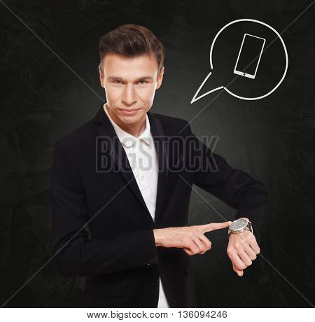 Time to make a call. Businessman in suit points at his watch at black background, thinking cloud with cell phone symbol. Modern mobile device, smartphone communication concept