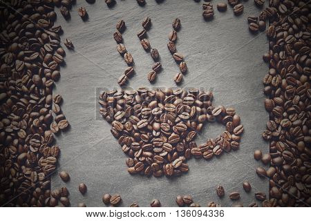 Cup from coffee beans with smoke. Heap of roasted coffee bean on grey stone surface texture. Coffee shop or cafe background. Natural stone and cup from beans. Soft color toning, top view