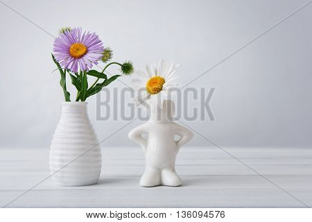 Beautiful aster amellus bouquet on white table at neutral background. Aster flower bouquet in white ceramic vase and camomile daisy in small vase in form of man. Flowers with copy space.