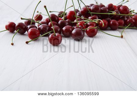 Sweet fresh scattered cherries. Fruits closeup on white rustic wood pattern with copy space. Healthy food background.