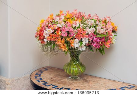 Flowers in glass vase on a table. Fresh design. Alstroemeria.