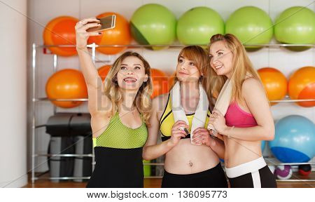 Making selfie. Group of girls in fitness class at the break looking at cell phone, happy and smiling. Woman friendship, healthy modern life of young people concept.