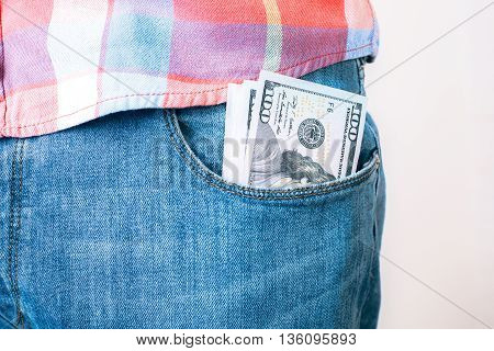 Bribery and corruption concept with dollar banknotes in jeans pocket