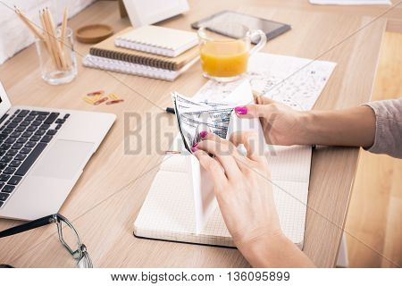 Woman counting money above wooden office desktop with various items. Bribery and corruption concept