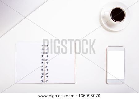 Top view of white office desktop with blank spiral notepad cell phone coffee cup and closed laptop. Mock up