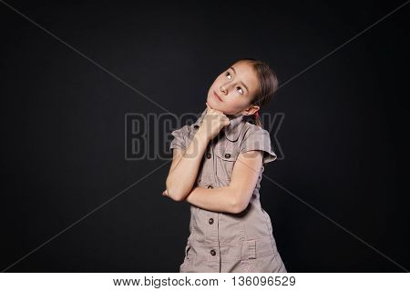 Thinking child portrait. Little preteen girl pensive, consider something, looking up. Primary school student solving some problem at black studio background with copy space.