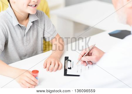 Do not forget to take medication. Close up of doctor sitting at desk, making record in history of patient and smiling boy, holding pills in hand