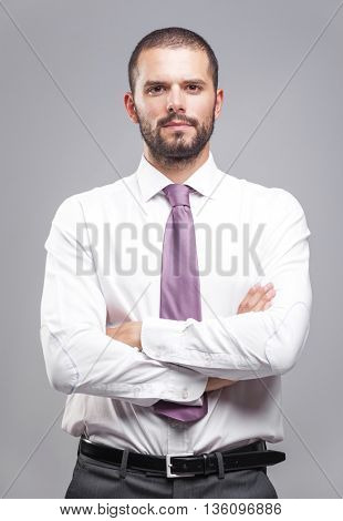 Portrait of young serious business man on grey background