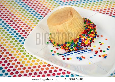 Upside down cupcake with birthday candle and colorful candy sprinkles on white square plate.