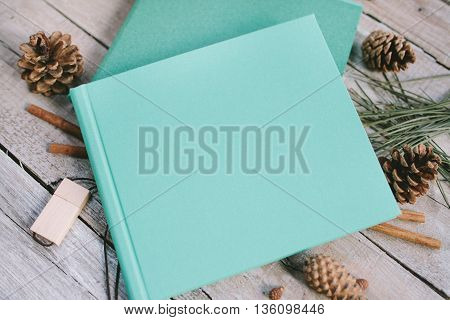 The blue book on a wooden background with cones and cinnamon. The big book on wooden boards. Wooden flash card.