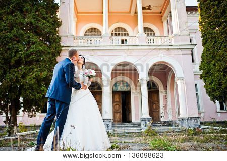 Stylish Wedding Couple Near Old Vintage Pink House With Columns