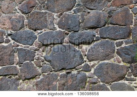 Texture is very old stone walls of the fortress. The wall of the medieval fortress of large stones. Background of cobblestones. The ancient construction of buildings from natural stones.