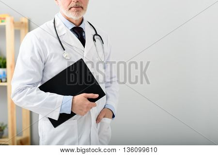Your health is my number one priority. Portrait of mature doctor using notepad, standing near copy space